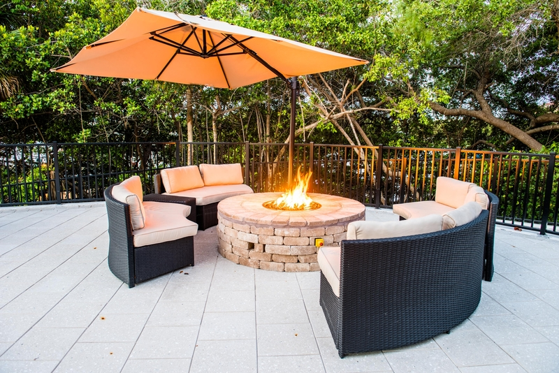 View of a fire pit next to the tropical courtyard and pool at Tarpon Cove Yacht & Racquet Club in Naples, Florida